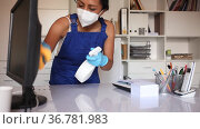 Professional female worker of office cleaning service wearing protective face mask and rubber gloves wiping desk with disinfectant. Стоковое видео, видеограф Яков Филимонов / Фотобанк Лори