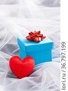 Blaues Geschenk mit Roter Schleife und Herz auf Hochzeitsschleier. Стоковое фото, фотограф Zoonar.com/Ulrich Schade / easy Fotostock / Фотобанк Лори