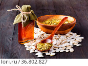 Pumpkin seeds and on the table, virgin pumpkin oil in a glass jar. Стоковое фото, фотограф Zoonar.com/Photographer: Andrey N.Cherkasov / easy Fotostock / Фотобанк Лори