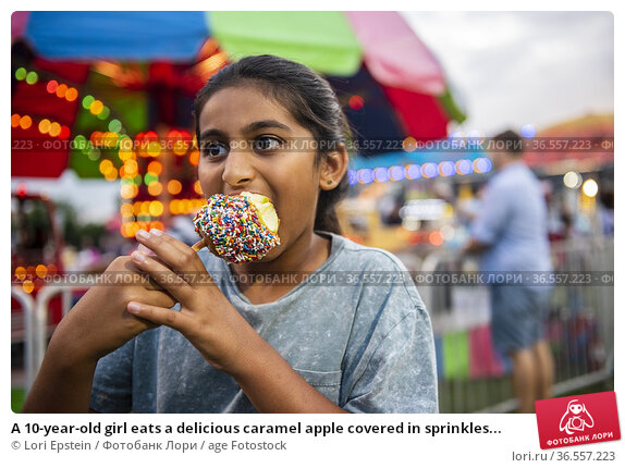 A 10-year-old girl eats a delicious caramel apple covered in sprinkles... Стоковое фото, фотограф Lori Epstein / age Fotostock / Фотобанк Лори