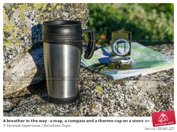 Купить «A breather in the way - a map, a compass and a thermo cup on a stone on a natural background», фото № 28841227, снято 21 июля 2018 г. (c) Евгений Харитонов / Фотобанк Лори