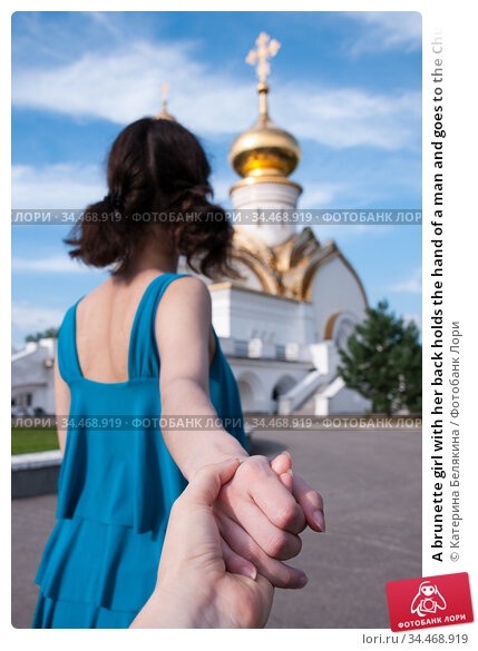 A brunette girl with her back holds the hand of a man and goes to the Church in the summer, the concept of religion. Стоковое фото, фотограф Катерина Белякина / Фотобанк Лори