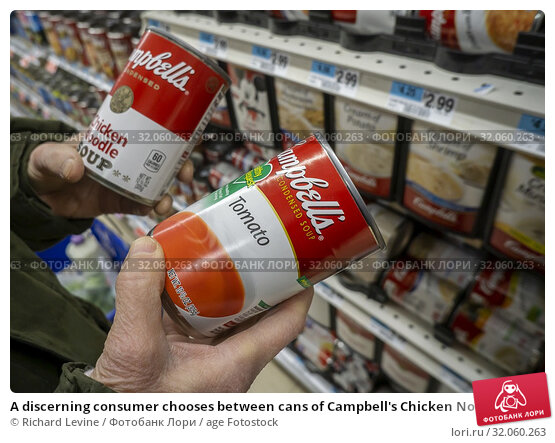 A discerning consumer chooses between cans of Campbell's Chicken Noodle and Tomato Soups in a supermarket in New York on Tuesday, February 26, 2019. (© Richard B. Levine). Редакционное фото, фотограф Richard Levine / age Fotostock / Фотобанк Лори