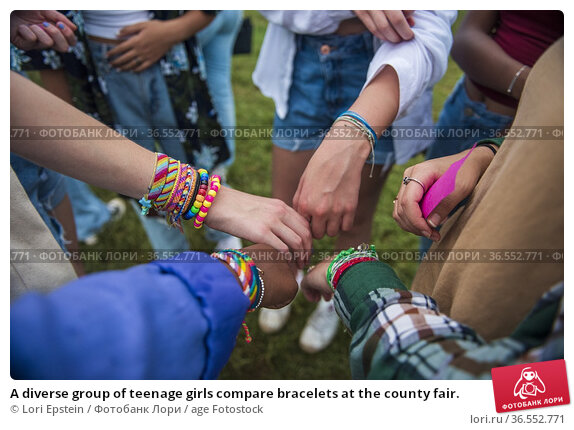 A diverse group of teenage girls compare bracelets at the county fair. Стоковое фото, фотограф Lori Epstein / age Fotostock / Фотобанк Лори
