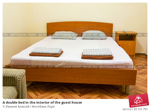Купить «A double bed in the interior of the guest house», фото № 33131751, снято 9 июля 2020 г. (c) Иванов Алексей / Фотобанк Лори
