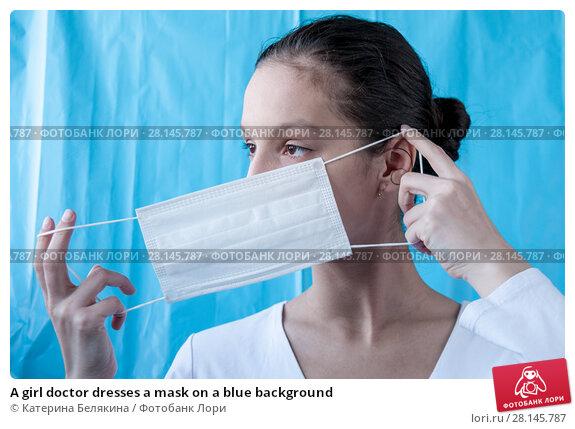Купить «A girl doctor dresses a mask on a blue background», фото № 28145787, снято 18 февраля 2018 г. (c) Катерина Белякина / Фотобанк Лори