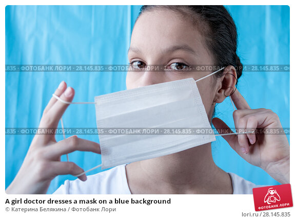 Купить «A girl doctor dresses a mask on a blue background», фото № 28145835, снято 18 февраля 2018 г. (c) Катерина Белякина / Фотобанк Лори