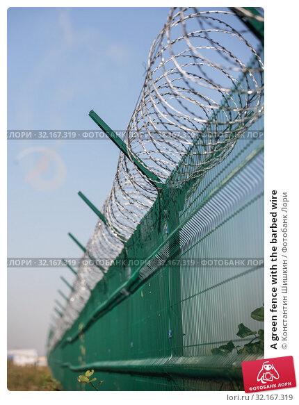Купить «A green fence with the barbed wire», фото № 32167319, снято 30 августа 2019 г. (c) Константин Шишкин / Фотобанк Лори