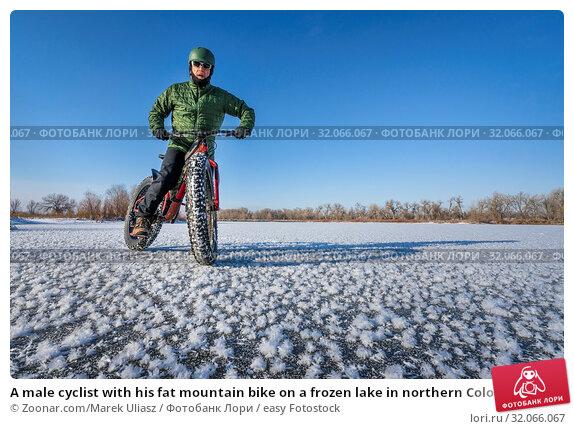 A male cyclist with his fat mountain bike on a frozen lake in northern Colorado. Стоковое фото, фотограф Zoonar.com/Marek Uliasz / easy Fotostock / Фотобанк Лори
