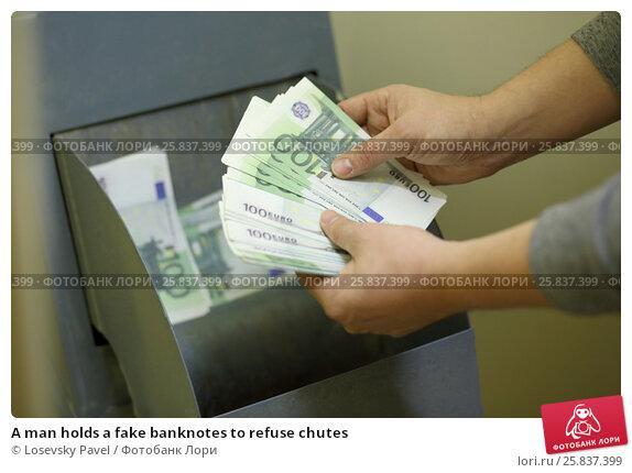 Купить «A man holds a fake banknotes to refuse chutes», фото № 25837399, снято 1 мая 2015 г. (c) Losevsky Pavel / Фотобанк Лори