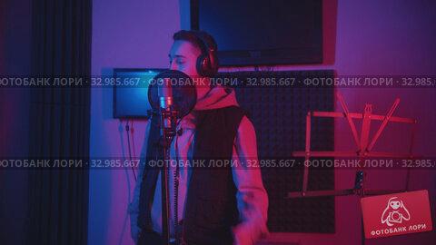 Купить «A man in headphones wearing a hoodie rapping through the pop-filter in the microphone - recording his track in the studio - music stand on the foreground», видеоролик № 32985667, снято 4 апреля 2020 г. (c) Константин Шишкин / Фотобанк Лори