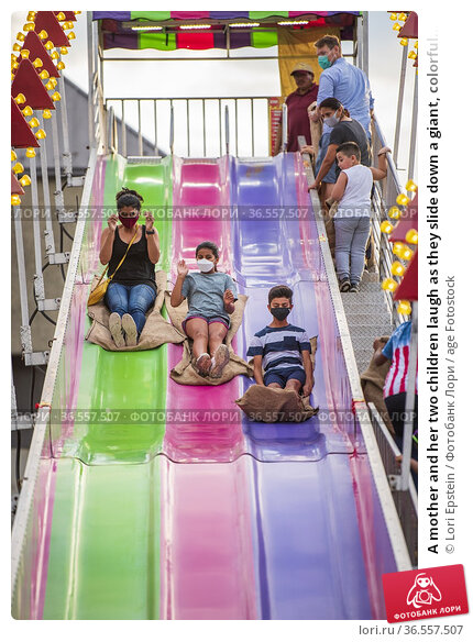 A mother and her two children laugh as they slide down a giant, colorful... Редакционное фото, фотограф Lori Epstein / age Fotostock / Фотобанк Лори