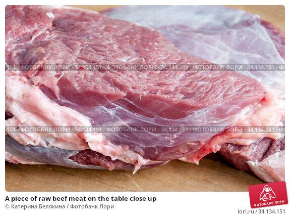 Купить «A piece of raw beef meat on the table close up», фото № 34134151, снято 26 мая 2020 г. (c) Катерина Белякина / Фотобанк Лори