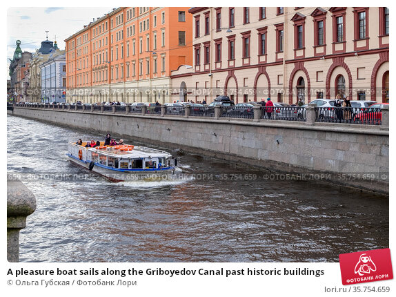 A pleasure boat sails along the Griboyedov Canal past historic buildings. Редакционное фото, фотограф Ольга Губская / Фотобанк Лори