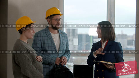 A pregnant woman with her husband looking out in new draft apartment - a man talking to a real estate agent. Стоковое видео, видеограф Константин Шишкин / Фотобанк Лори