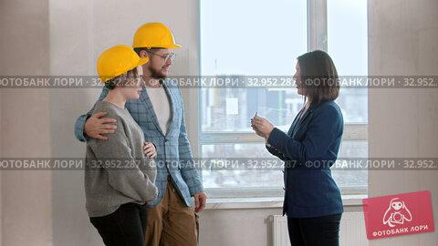 A real estate agent gives the keys to apartment to a young family. Стоковое видео, видеограф Константин Шишкин / Фотобанк Лори