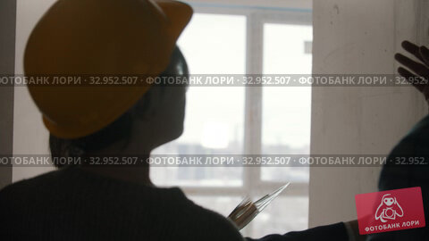 A real estate agent showing a new draft apartment to a family - pointing at the ceiling. Стоковое видео, видеограф Константин Шишкин / Фотобанк Лори