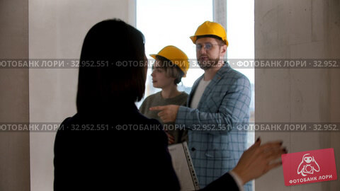 A real estate agent showing a new draft apartment to a young family - the married couple looking around. Стоковое видео, видеограф Константин Шишкин / Фотобанк Лори