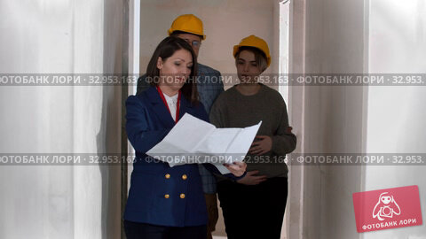 A real estate agent showing a new draft apartment to a young successful married couple in helmets holding a layout on the paper. Стоковое видео, видеограф Константин Шишкин / Фотобанк Лори