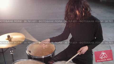 Купить «A rock group having a repetition. A man with cool long hair playing drums», видеоролик № 30761651, снято 24 мая 2019 г. (c) Константин Шишкин / Фотобанк Лори