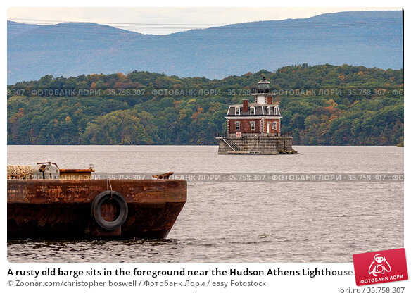 A rusty old barge sits in the foreground near the Hudson Athens Lighthouse... Стоковое фото, фотограф Zoonar.com/christopher boswell / easy Fotostock / Фотобанк Лори