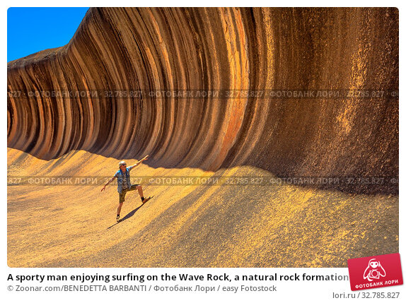 A sporty man enjoying surfing on the Wave Rock, a natural rock formation that is shaped like a tall breaking ocean wave, in Hyden, Western Australia. Happy funny male in Australian outback. Стоковое фото, фотограф Zoonar.com/BENEDETTA BARBANTI / easy Fotostock / Фотобанк Лори