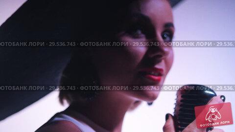 Купить «A woman in big black elegant hat grabs the mic and starts singing», видеоролик № 29536743, снято 10 декабря 2018 г. (c) Константин Шишкин / Фотобанк Лори