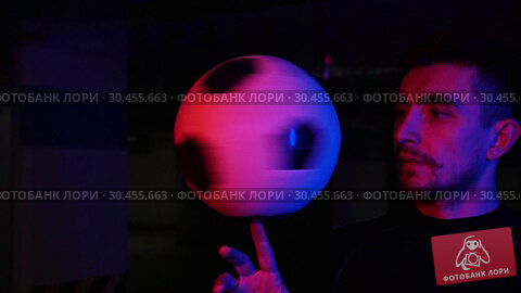 A young man on the underground parking spinning the ball on his finger in neon lighting. Стоковое видео, видеограф Константин Шишкин / Фотобанк Лори