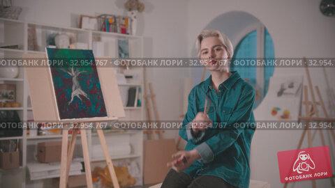 A young woman artist sits on the chair on the art studio. Стоковое видео, видеограф Константин Шишкин / Фотобанк Лори