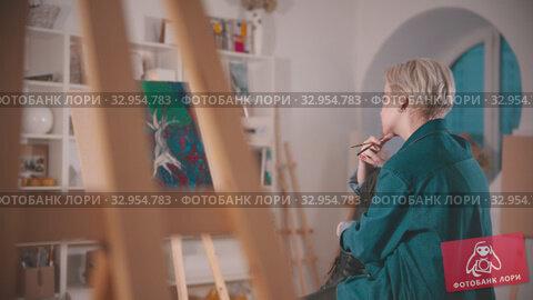 Купить «A young woman artist with short blonde hair sitting in the art studio - looking at her painting from the distance», видеоролик № 32954783, снято 26 мая 2020 г. (c) Константин Шишкин / Фотобанк Лори