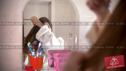 A young woman brushes her hair looking in the mirror. Стоковое видео, видеограф Константин Шишкин / Фотобанк Лори