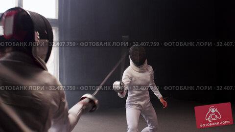 Купить «A young woman fencer walking to the fighting area and starts the duel», видеоролик № 32407759, снято 3 апреля 2020 г. (c) Константин Шишкин / Фотобанк Лори