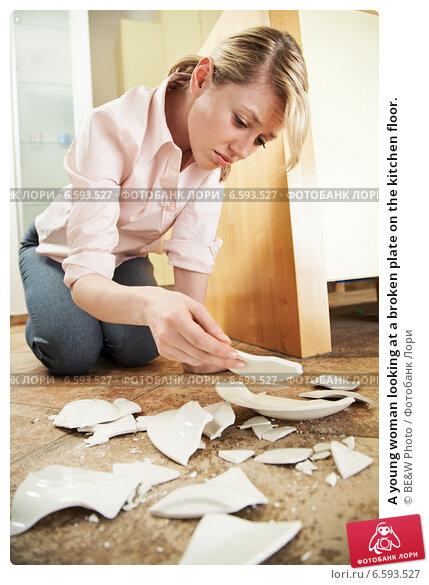Купить «A young woman looking at a broken plate on the kitchen floor.», фото № 6593527, снято 11 января 2018 г. (c) Joanna Malesa / Фотобанк Лори