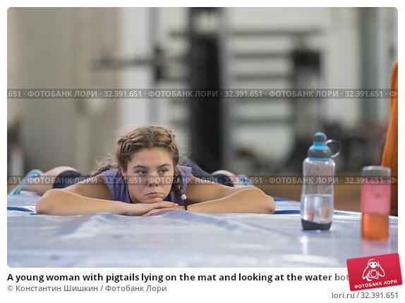 Купить «A young woman with pigtails lying on the mat and looking at the water bottle», фото № 32391651, снято 1 ноября 2019 г. (c) Константин Шишкин / Фотобанк Лори