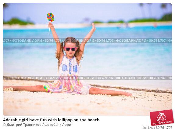 Купить «Adorable girl have fun with lollipop on the beach», фото № 30761707, снято 30 марта 2015 г. (c) Дмитрий Травников / Фотобанк Лори