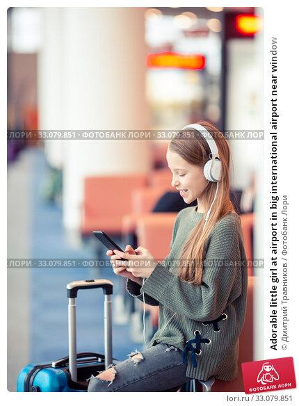 Купить «Adorable little girl at airport in big international airport near window», фото № 33079851, снято 25 марта 2019 г. (c) Дмитрий Травников / Фотобанк Лори