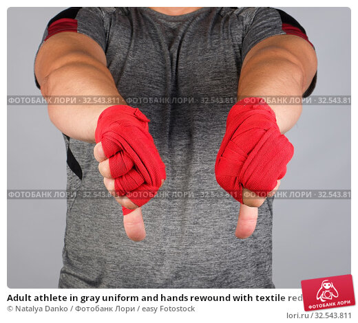 Купить «Adult athlete in gray uniform and hands rewound with textile red bandage shows gesture dislike, white background.», фото № 32543811, снято 4 июля 2019 г. (c) easy Fotostock / Фотобанк Лори