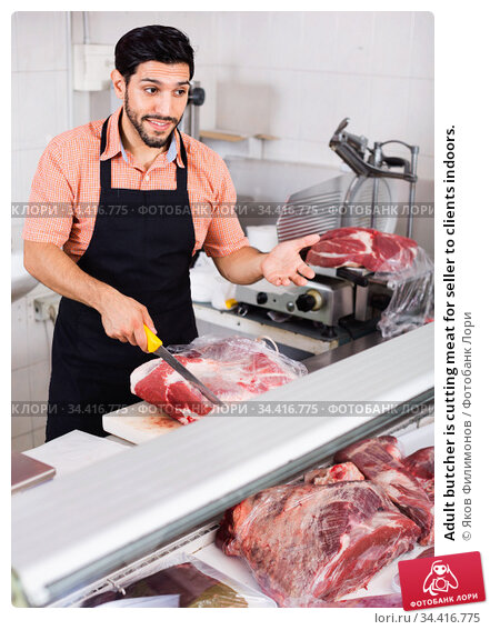 Adult butcher is cutting meat for seller to clients indoors. Стоковое фото, фотограф Яков Филимонов / Фотобанк Лори