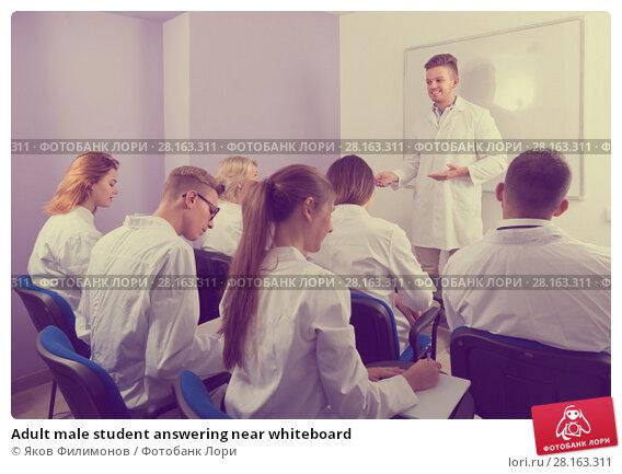 Купить «Adult male student answering near whiteboard», фото № 28163311, снято 5 октября 2017 г. (c) Яков Филимонов / Фотобанк Лори