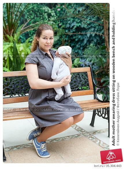 Adult mother wearing dress sitting on wooden bench and holding hands newborn baby, full-length portrait. Стоковое фото, фотограф Кекяляйнен Андрей / Фотобанк Лори