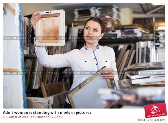 Adult woman is standing with modern pictures. Стоковое фото, фотограф Яков Филимонов / Фотобанк Лори