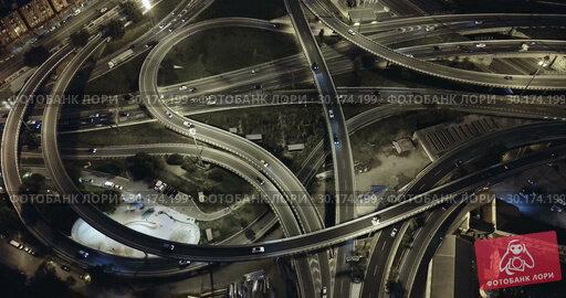 Купить «Aerial view of lighted highway road junctions at night», видеоролик № 30174199, снято 26 октября 2018 г. (c) Яков Филимонов / Фотобанк Лори