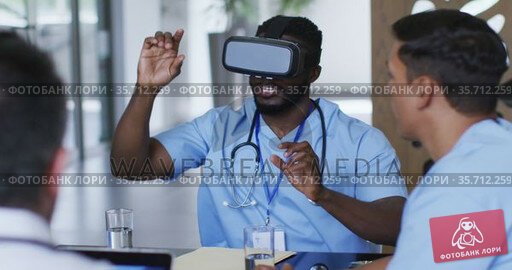 African american male doctor at table using vr headset with a diverse group of colleagues watching. Стоковое видео, агентство Wavebreak Media / Фотобанк Лори