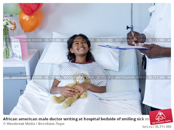 African american male doctor writing at hospital bedside of smiling sick mixed race girl. Стоковое фото, агентство Wavebreak Media / Фотобанк Лори