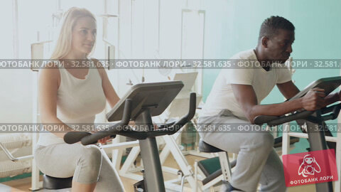 Купить «African man and Caucasian woman exercising on stationary bikes at gym», видеоролик № 32581635, снято 24 марта 2019 г. (c) Яков Филимонов / Фотобанк Лори