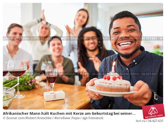 Afrikanischer Mann hält Kuchen mit Kerze am Geburtstag bei seiner... Стоковое фото, фотограф Zoonar.com/Robert Kneschke / age Fotostock / Фотобанк Лори
