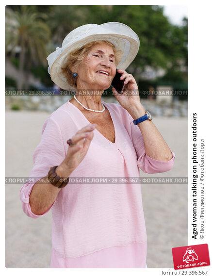 Купить «Aged woman talking on phone outdoors», фото № 29396567, снято 6 июля 2018 г. (c) Яков Филимонов / Фотобанк Лори