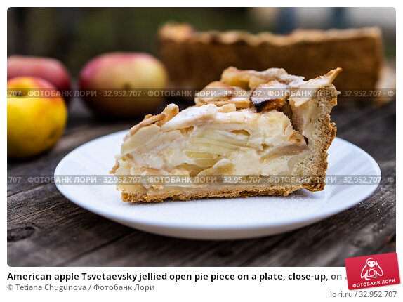 American apple Tsvetaevsky jellied open pie piece on a plate, close-up, on a dark wooden background. Flat lay. Стоковое фото, фотограф Tetiana Chugunova / Фотобанк Лори
