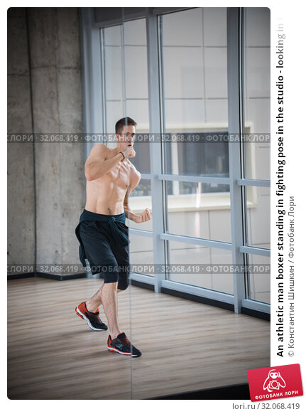 An athletic man boxer standing in fighting pose in the studio - looking in the mirror. Стоковое фото, фотограф Константин Шишкин / Фотобанк Лори