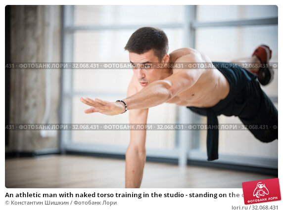 An athletic man with naked torso training in the studio - standing on the one hand. Стоковое фото, фотограф Константин Шишкин / Фотобанк Лори